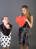 Two happy girls. Holding red heart Stock Image