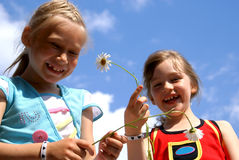 Two happy girls. Two laughing girls hold in camomile hands flowers - camomiles against the sky Stock Photo