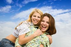 Two happy girls. Together against cloudy sky Stock Photography