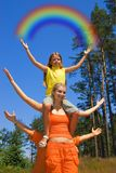 Two happy girls. Small girl sitting on a sister's shoulders  holding  rainbow in her hands Stock Image