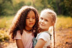 Two happy girls as friends hug each other in cheerful way. Little girlfriends in park. Royalty Free Stock Photography