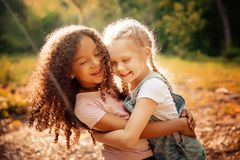 Two happy girls as friends hug each other in cheerful way. Little girlfriends in park. Royalty Free Stock Photo