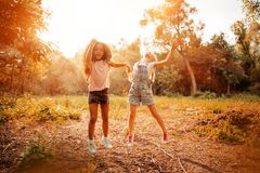 Two happy girls as friends hug each other in cheerful way. Little girlfriends in park. Children Friendship Together Smiling Happiness Concept Stock Image