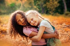 Two happy girls as friends hug each other in cheerful way. Little girlfriends in park. Royalty Free Stock Photos