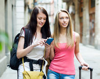 Two happy girls with bags using the navigator Stock Photography