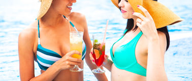 Two happy girls with beverages on summer party near the pool, cl stock photography