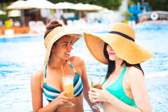 Two happy girls with beverages on summer party near the pool stock photography