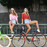 Two happy girls with bicycles Stock Images