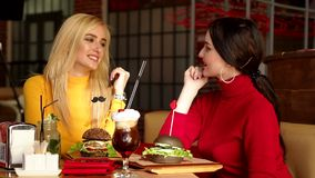 Two smiling girls drink cocktails and eat burgers in a bright restaurant. stock footage