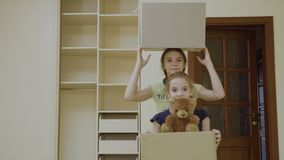 Two happy girls with boxes relocates in a new house. Pretty sisters stands in front of camera in a new room and elder sister slowly stands up behind her sister stock footage