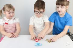 Two happy girls and boy play with spinners on table. In white studio Stock Photography