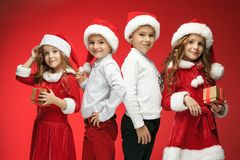Two happy girls and boys in santa claus hats with gift boxes Stock Photo