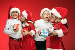 Two happy girls and boys in santa claus hats with gift boxes at studio Royalty Free Stock Images