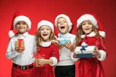 Two happy girls and boys in santa claus hats with gift boxes at studio Royalty Free Stock Photography