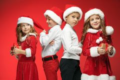 Two happy girls and boys in santa claus hats with gift boxes at studio Stock Photos