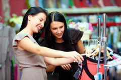 Two happy girls buy dress on store sale Royalty Free Stock Photography