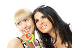 Two happy girls with a candy Stock Photography