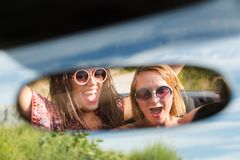 Two happy girls in a car rear-view mirror. Stock Photo
