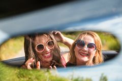 Two happy girls in a car rear-view mirror. Stock Image