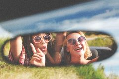 Two happy girls in a car rear-view mirror. Royalty Free Stock Photos