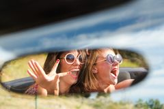 Two happy girls in a car rear-view mirror. Stock Photos