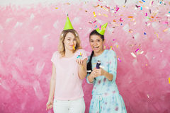 Two happy girls celebrate birthday party with cupcake confetti a. Two happy expressive girls celebrate birthday party with cupcake, confetti and caps over pink Stock Photo