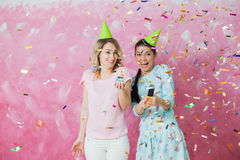 Two happy girls celebrate birthday party with cupcake confetti a. Two happy expressive girls celebrate birthday party with cupcake, confetti and caps over pink Royalty Free Stock Images