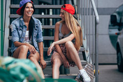 Two happy girls chatting on stairs Royalty Free Stock Photography