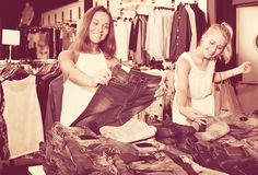 Two happy girls choosing denim trousers Stock Images