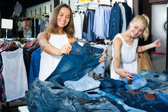 Two happy girls choosing denim trousers Stock Photography