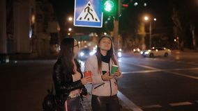 Two happy girls in the city at night at a traffic light, drinking coffee from paper cups and talking. stock footage