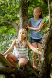 Two happy girls climbing up tree in summer park Royalty Free Stock Photo