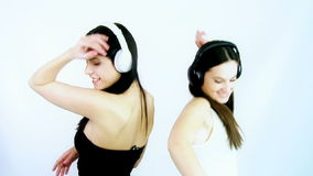 Two happy girls dancing happy listening music. Two female model listening music with headset dancing stock video