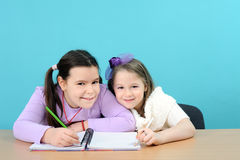 Two happy girls doing their school work Stock Photos