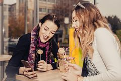 Two happy girls eating cakes and looking at pictures on a mobil royalty free stock photos