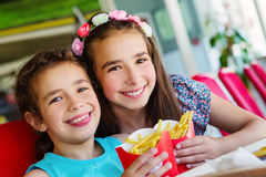 Two happy girls in fast food restaurant Royalty Free Stock Image