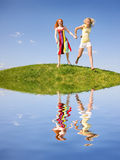 Two happy girls fleeing on a meadow. Reflected in water. Against the backdrop of blue sky Stock Photo
