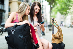 Two happy girls with GPS navigator and baggage. Outdoor. Focus on blonde Royalty Free Stock Photography