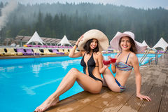 Two happy girls in a hats sitting on the edge of the swimming pool and drinking cocktails, looking to the camera. On the background of mighty forests Stock Photography