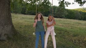 Two happy girls on rope swing - slow mo stock footage