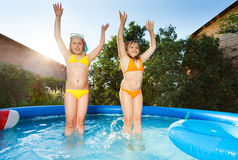 Two happy girls having fun in the swimming pool Stock Photo
