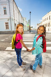Two happy girls hold hands, stand near crossroad Stock Photo