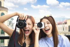 happy girls holding camera and travel concept stock photo