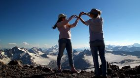 Two happy girls hugging in the top of the mountain with his arms. Raised above his head in celebration of reaching stock footage