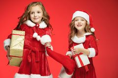 Two Happy Girls In Santa Claus Hats With Gift Boxes At Studio Stock Photo
