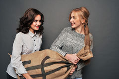 Two happy girls and insidious drag bag. Stock Photography