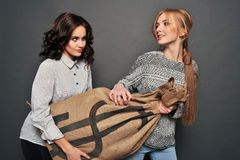 Two happy girls and insidious drag bag. Stock Images