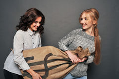 Two happy girls and insidious drag bag. Stock Photo