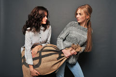Two happy girls and insidious drag bag. Royalty Free Stock Photography