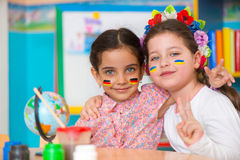Two happy girls in international summer camp. With flags on cheeks Royalty Free Stock Photography